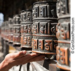 Prayer wheels and a hand