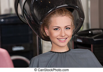 blond women at hairdresser while drying under hairdryer....