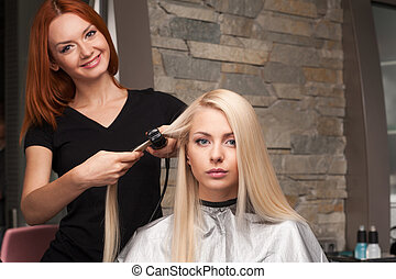 Happy young woman getting new haircut by hairdresser at parlor. redhead hairdresser straightening client's hair in beauty salon