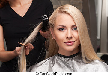 closeup on happy young woman getting new haircut by hairdresser at parlor. hairdresser straightening client's hair in beauty salon