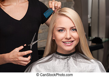 Happy young woman getting new haircut by hairdresser at...