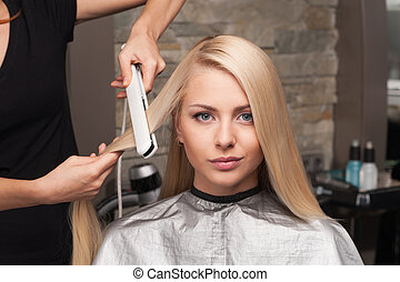 closeup on young woman getting new haircut by hairdresser at...