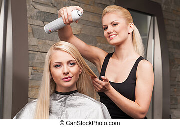 blond hairdresser applying spray on client's hair and looking into camera. Female hairdresser works on woman hair in salon
