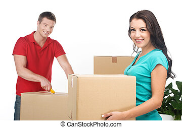 Couple moving boxes and unpacking stuff. happy young couple...