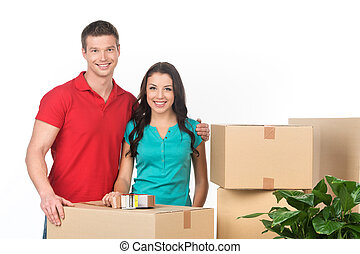Young couple on moving day carrying cardboard boxes. Smiling...