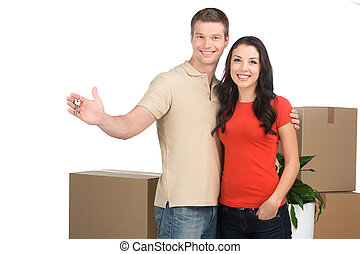 couple celebrating new home with keys and moving boxes....