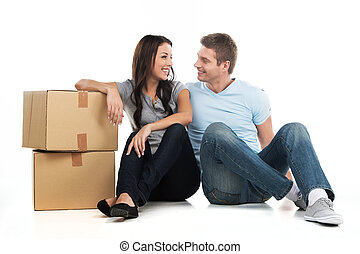 Young smiling couple moving in new house man and woman...