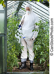Garden worker in protective clothing spraying plants