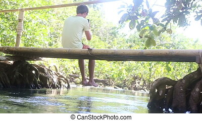 man sitting on the bridge with his legs dangling under which...