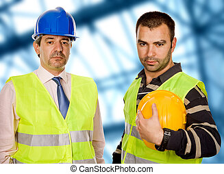 workers - proud boss and worker standing looking at the...