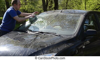 man clean automobile - Young man carefully wash his...