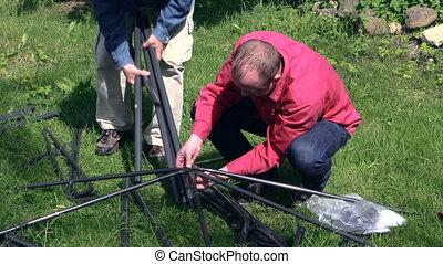 men build arbour - Two men building construction bower roof...