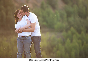 Young woman gets a kiss from her man