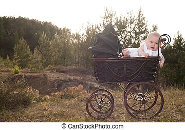 Baby in pram with sunset - Baby girl is sitting in a vintage...