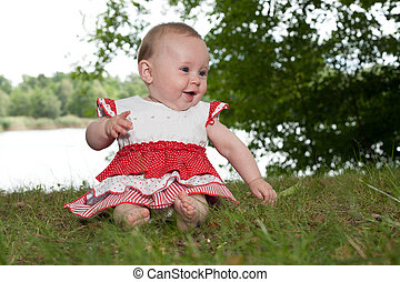 Happy baby in anture - Little baby girl is sitting and...