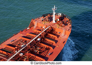 Large red cargo ship driving on deep blue ocean - Bow of a...
