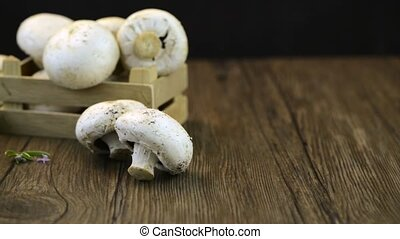Champignons in a wooden box on dark boards.