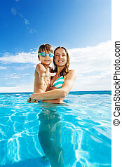 Mother holds son with goggles and smiles in pool - Mother...