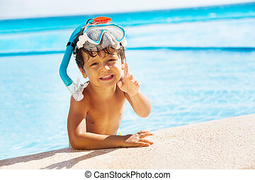 Boy with snorkel mask on head and pointing finger - Smiling...