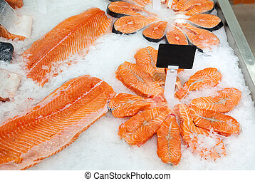 Slices of fresh raw salmon in ice ready to sale at the...