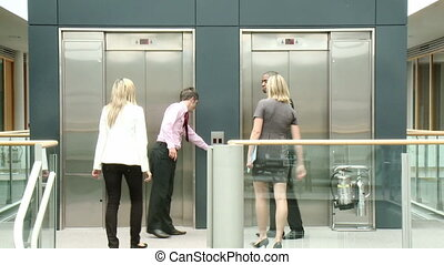 Business people using a lift in building - Attractive young...
