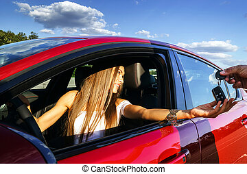 Young woman taking keys of new car - Young woman taking keys...