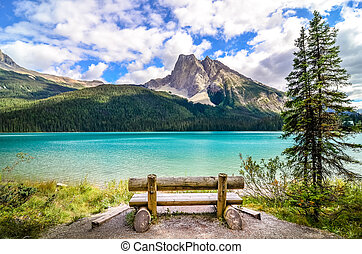 Scenic view of mountain lake and wooden bench