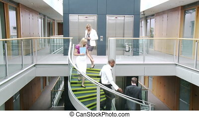 Business people going downstairs in office - Vertical...
