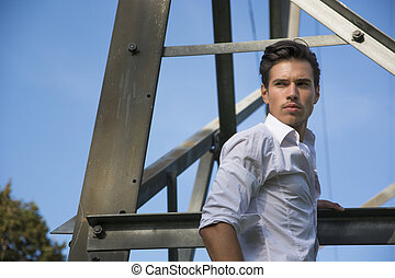 Handsome young man hanging from metal electricity trellis,...