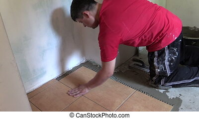 man tiling floor home - man work at home renovation with...