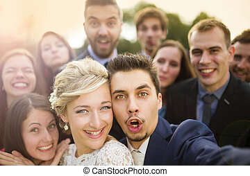 Newlyweds with friends taking selfie - Young couple of...