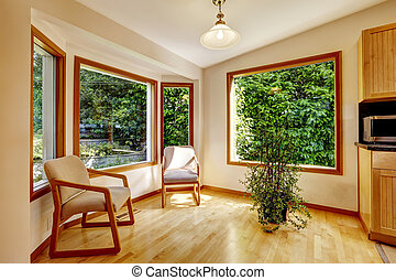 Sunroom interior with two chairs and decorative tree