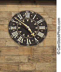 old gilded clock on stone wall in city