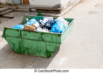 Big green overfilled trash dumpster