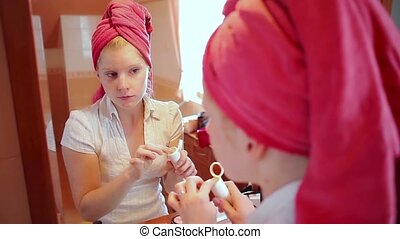 woman putting on make up - Young adult caucasian woman...