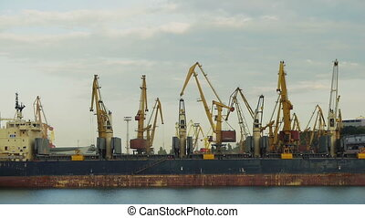 ODESSA - MAY 28: (TIME-LAPSE) Port cranes loading dry-cargo ship on May 26, 2013 in Odessa, Ukraine. Odessa port is one of the biggest ports located on the Black Sea coast.