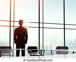 businessman standing in office - young businessman standing...