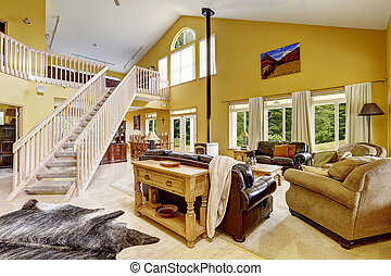 Luxury family room with rich furniture and staircase to loft