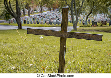 Wooden cross in a cemetary with hundreds of tombstones in the ba