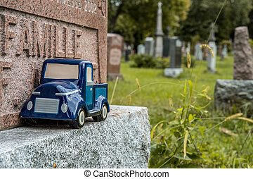 Blue car toy on a tombstone in a cemetary
