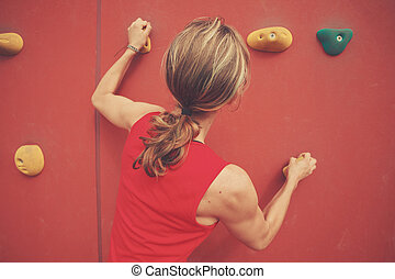Young woman bouldering - A young woman is scaling a...