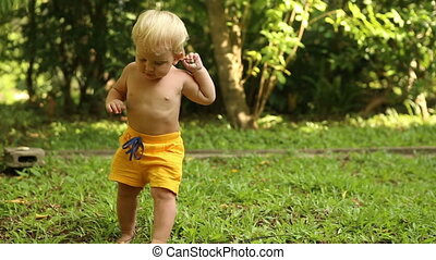 baby walking on the grass and digging in ground