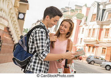 Beautiful couple of tourists holding a map in their hands,...