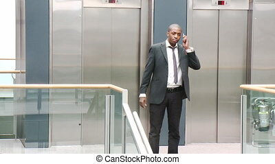 Afro-American businessman on phone in a building