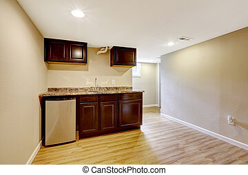 Empty basement room with dark brown kitchen cabinets....