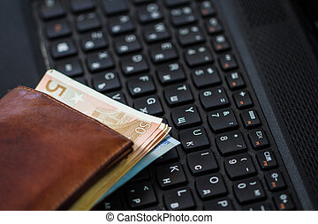 Wallet and  money on keyboard. Online banking.