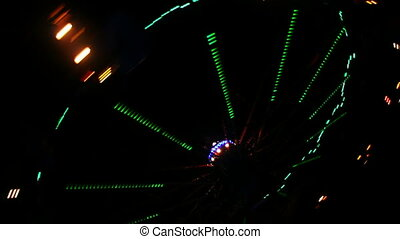 Amusement park at night, whirligig in motion