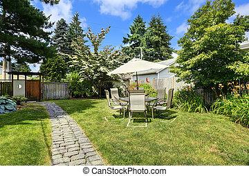 Backyad with brick tile walkway and patio area