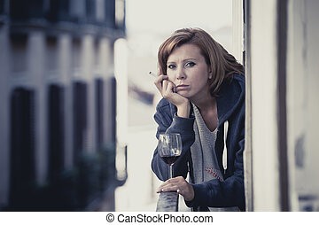 young woman suffering depression drinking wine outdoors at...