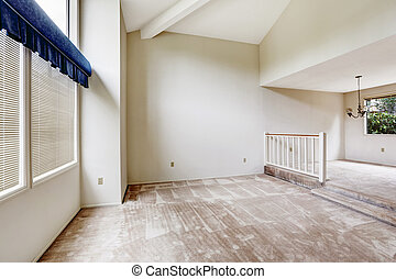 Empy house interior with high vaulted ceiling and carpet...